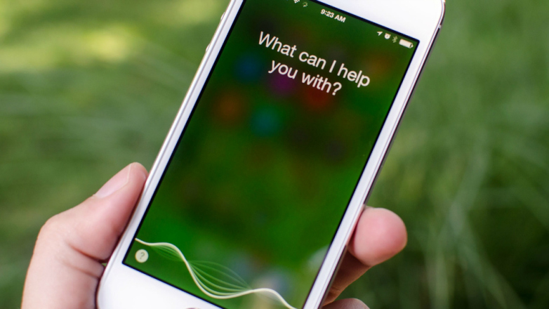 Close-up of a iPhone with Siri activated. It asks 'What can I help you with?' on the screen.
