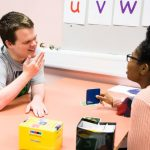 Student William communicating through hand gestures to a staff member