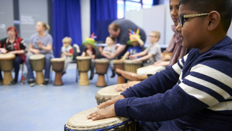 A side shot of kids taking part in a drumming session in Gallery Oldham.