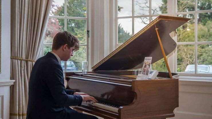 A young man sits playing a grand piano