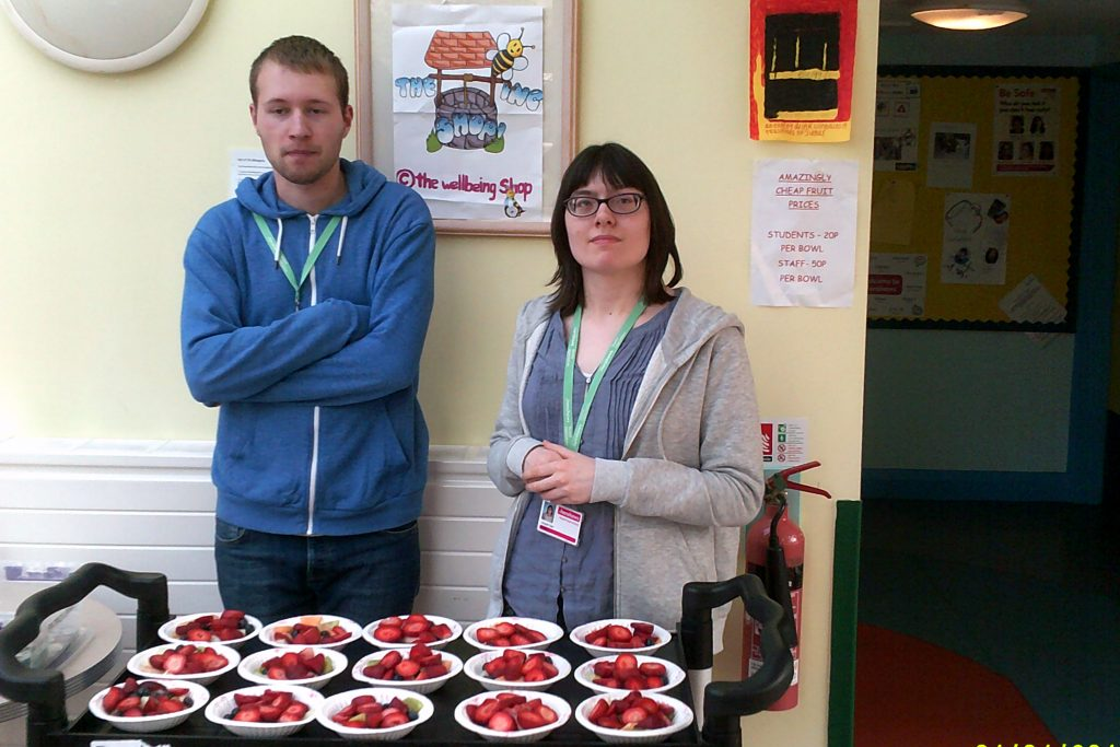 Students Alexander and Abigail standing in front of a trolley full of prepared strawberries, ready to be sold in the College.