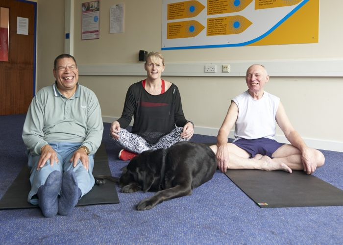 Two yoga students and their teacher sat at during their class.