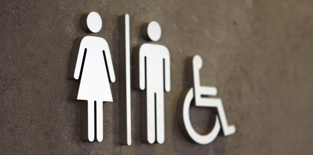 Close-up of a toilet sign with the symbols for woman, man and disabled user.