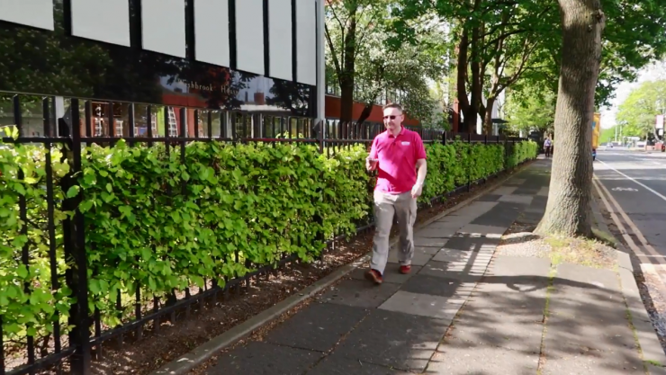 Shot of Mark walking on the pavement on a sunny day, holding his phone in front of him to use the Soundscape app.
