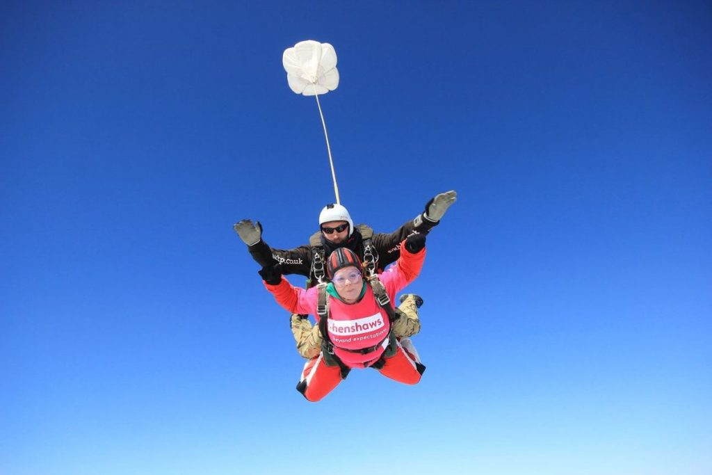 Amy during the freefall against a bright blue sky, and her tandem instructor behind her.