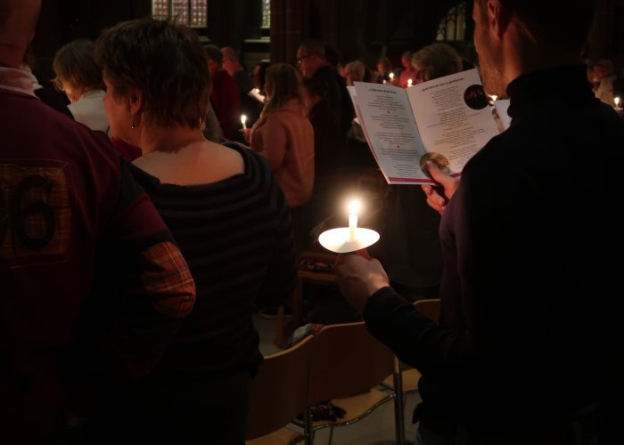 A man holding a candle and reading from a programme at the Carols by Candlelight concert