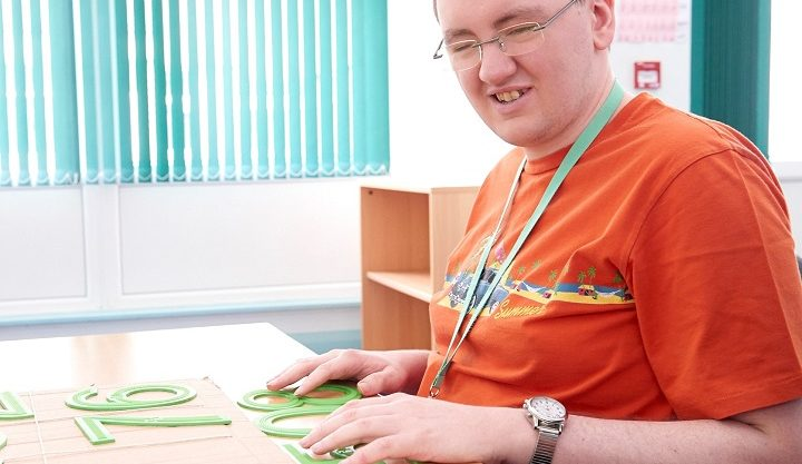 A man with a VI using braille numbers during his maths lesson at Henshaws Specialist College