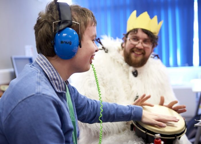 Sneosry storytelling of where the wild things are - a man dressed in a furry suit and with a paper crown with a younger man - both are playing a drum