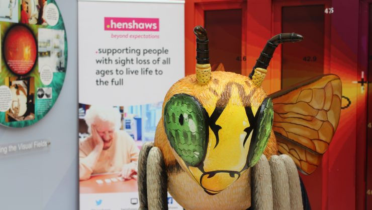 A close-up of the Bee at the hospital from front on; with the pull-up banner for Henshaws blurred in the back drop.