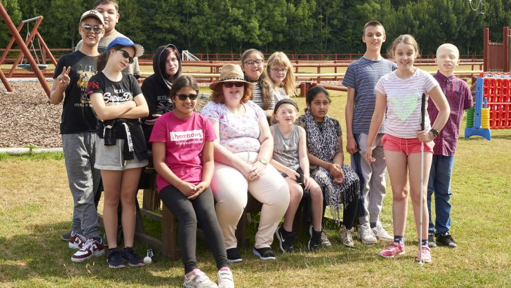 A group of children stood together smiling at the camera at the Adventure Farm Trip
