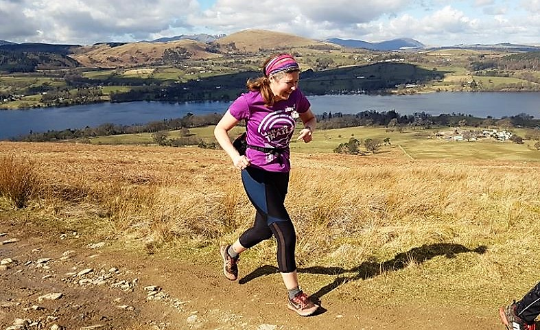 Fran running up a hill with a lakes and hills in the background. She is smiling remarkably!
