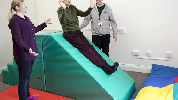 Male student on slide during sensory integration therapy session