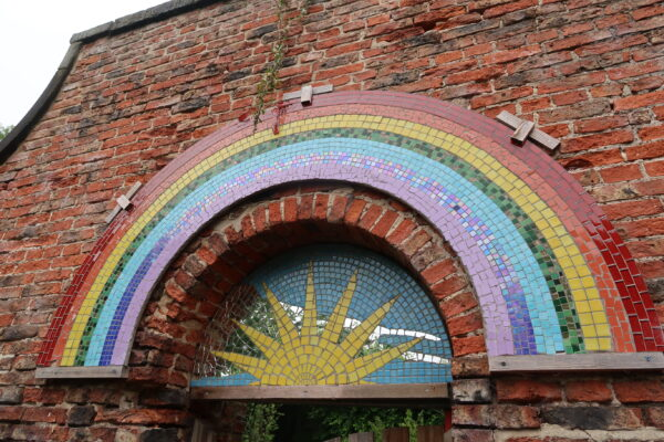 Rainbow mosaic and sunburst mirror which hangs above the entrance to the gardens, one of the hidden treasures of Henshaws Arts & Crafts Centre in Knaresborough