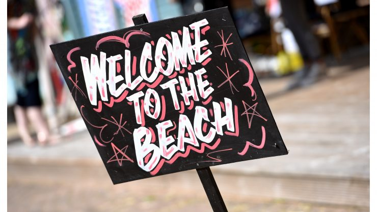 Sign at henshaws urban beach saying 'welcome to the beach' on a black chalkboard with white and magenta lettering