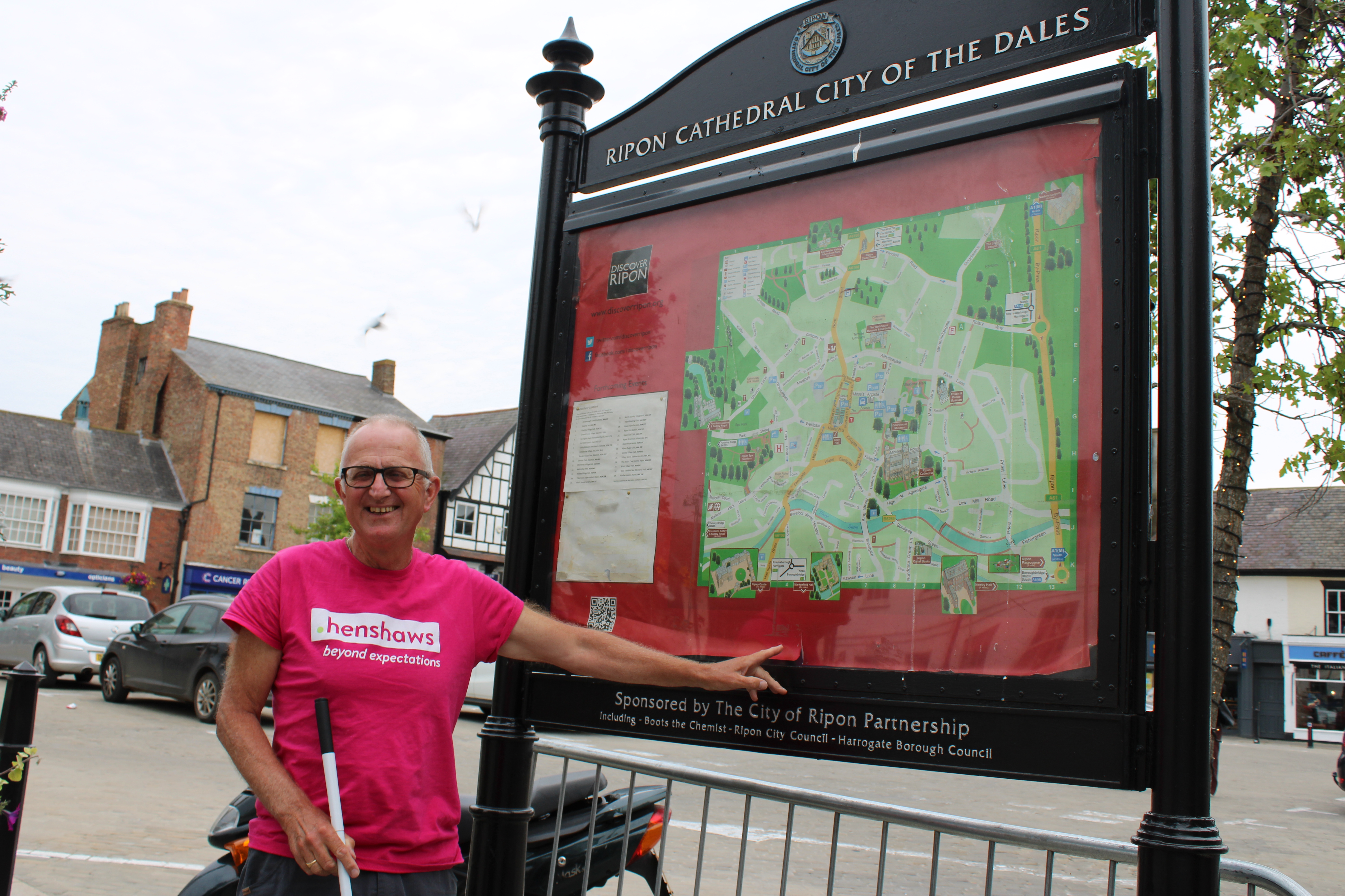 Dave stood in a pink Henshaws t-shirt smiling and pointing at a map of Ripon