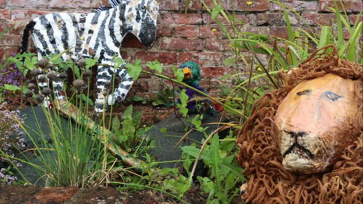 Paper mache zebra, frog and snake sculptures hide in the grass as part of Henshaws Animal Invasion