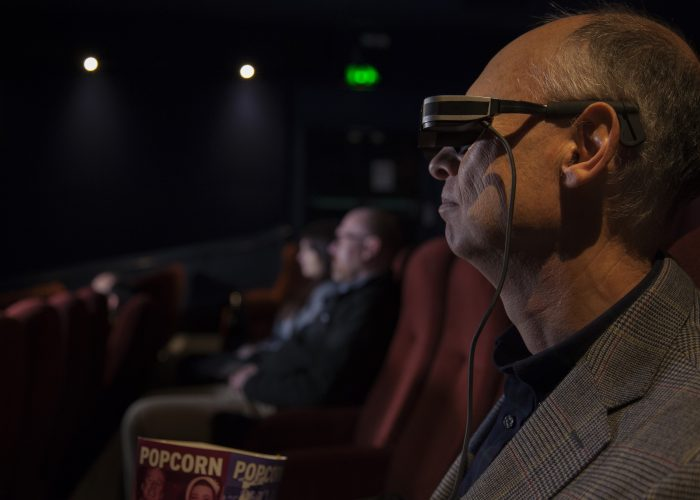 Gentleman with peripheral vision loss enjoying the theatre wearing OXSIGHT glasses