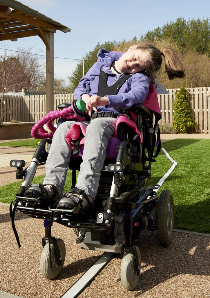 A disabled female in a wheelchair fitted with a switch