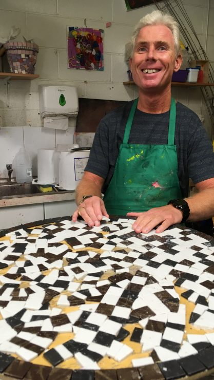Art Maker Andrew with his hand son the table top of a black, white and yellow mosaic he created for Henshaws 21 Exhibition