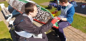 Two young men decorate a small boat with a mosaic