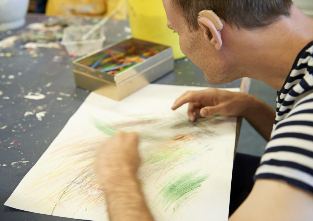 Chris mark making on paper using green and brown pencil crayons