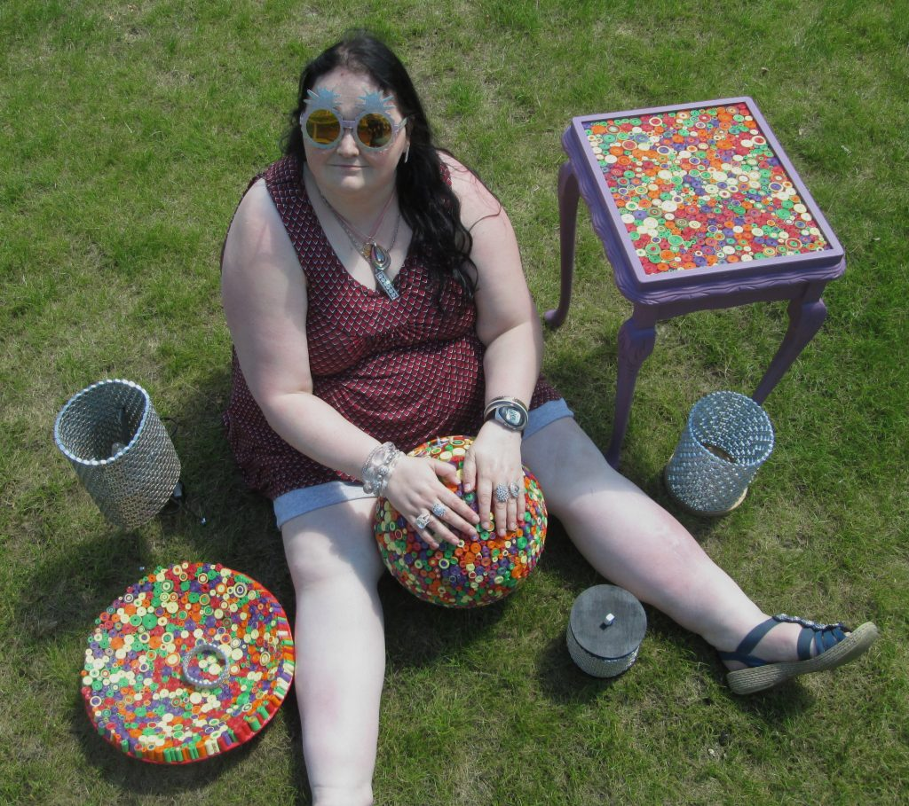 Art Maker Dolly sits on the grass surrounded by some of her artwork including stell nut lampshades and colourful embellished table tops