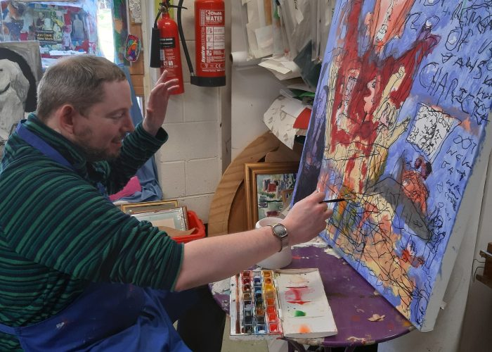 Art Maker Graham sits in front of an easel working on one of his paintings in the art studio