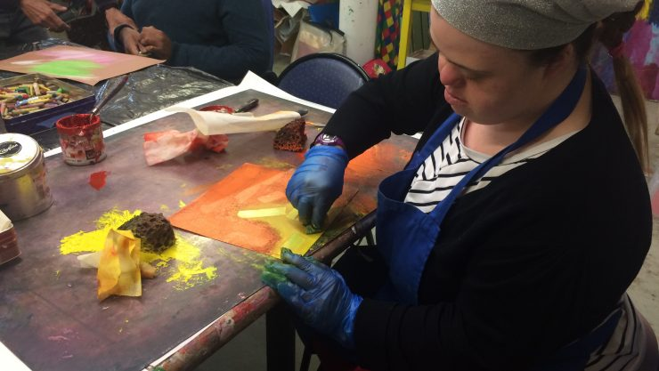 Art Maker Hannah sits painting in yellows and oranges in Henshaws art studio