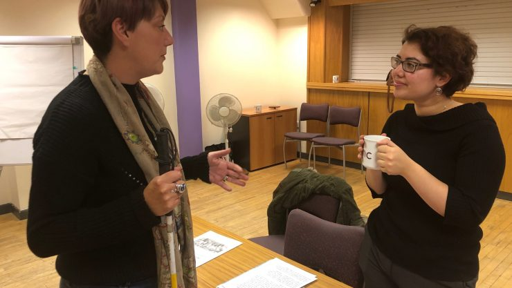 Image shows two women talking to each other over a cup of tea.