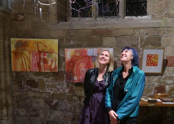 Organisers Sharon and Shaeron looking up at some of the artwork which deserves to be seen at Henshaws 21 Exhibition, including wire beaded hands and pen and ink colourful prints
