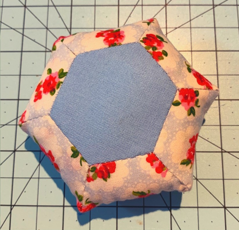 Image of hexagonal pin cushion created in floral and blue fabric as part of quilting workshop