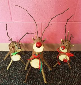 Three wooden reindeer stand side by side with twig antlers and decorations created in a Henshaws Handmade Christmas workshop
