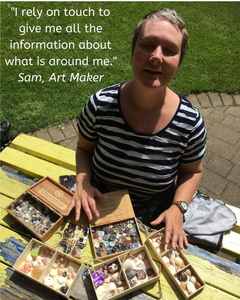 """Art Maker Sam sat at a picnic bench with some of her textured box artworks on display for Henshaws 21 Exhibition. Text quote reads """"I use touhc to give me all the information about what is around me"""""""