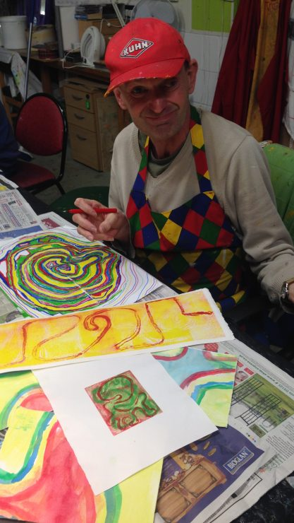 Art Maker Simon sits at a table with his colourful geometric painting designs in front of him in the art studio