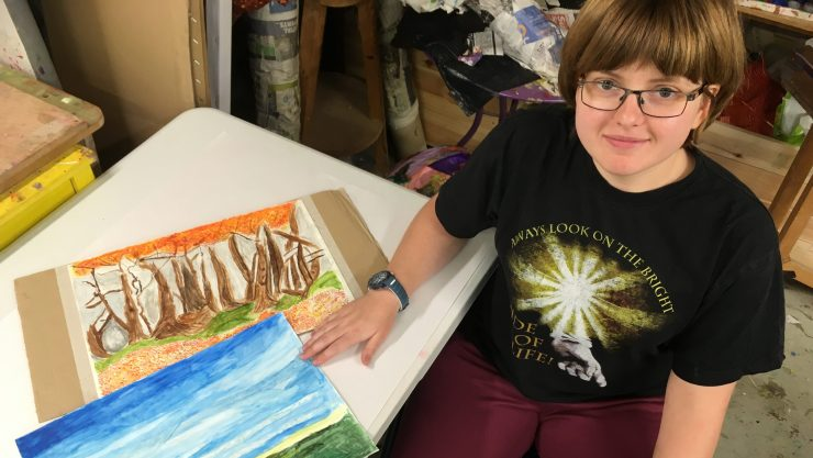 Art Maker Victoria sits in front of two of her paintings featuring a seascape and a forest in Henshaws art studio