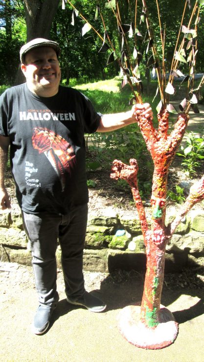 Art Maker Wesley stood next to his tree sculpture outside in Henshaws gardens