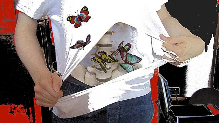 Abstract image of someone ripping open their t shirt to reveal a host of butterflies