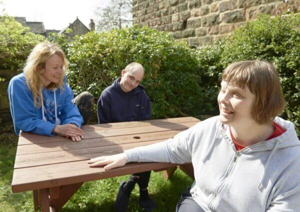 Three people sitting around a park bench
