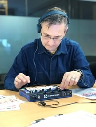 Mark sitting at a table playing with his groove box