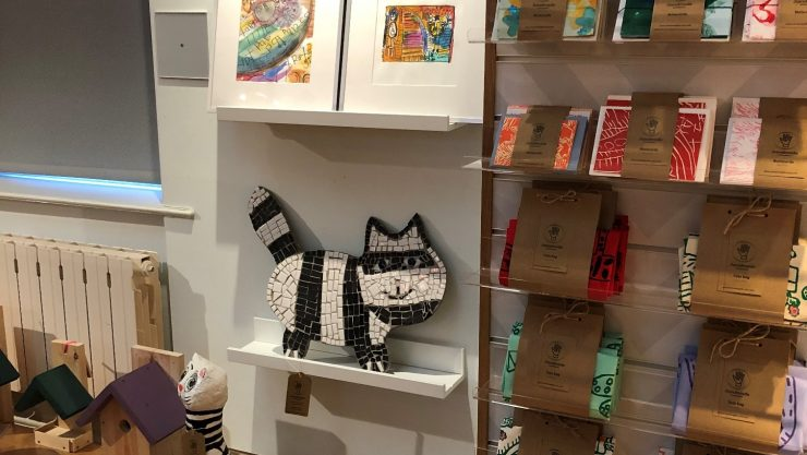 Display of products on sale at Henshaws Pop-Up Shop at the Mercer Art Gallery including tote bags, mosaics and prints