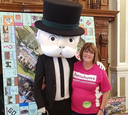 Community and Events Fundraiser Kate Simpson stands next to Mr Monopoly with the Harrogate board in the background