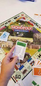 A hand holding a monopoly property card above the Harrogate monopoly board