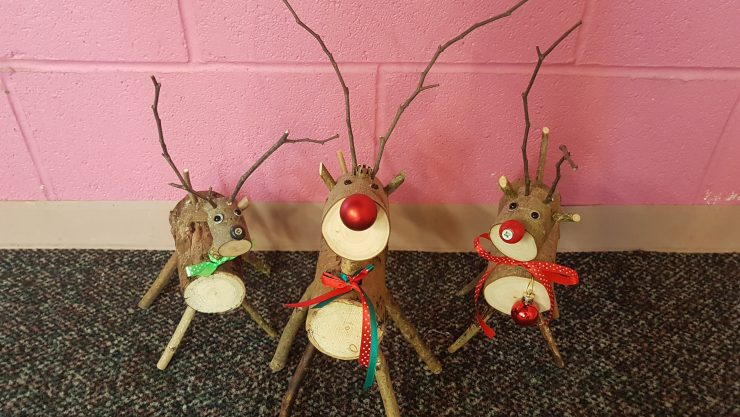Three wooden reindeer stand side by side