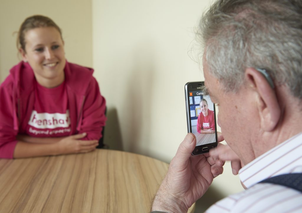 Image shows a member of Henshaws staff demonstrating some digital tech to an elderly gentleman.