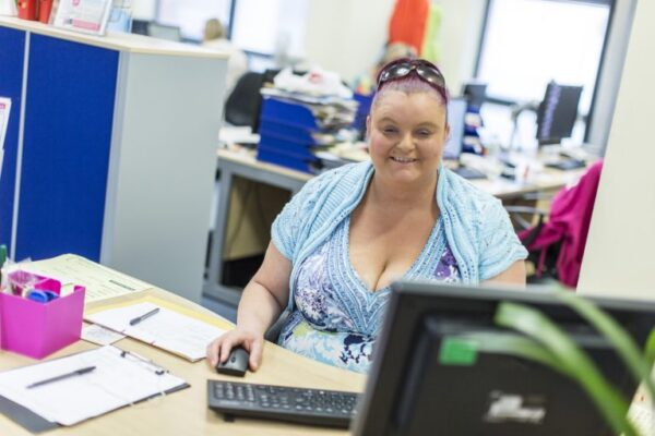 Lady working at a desk at Henshaws