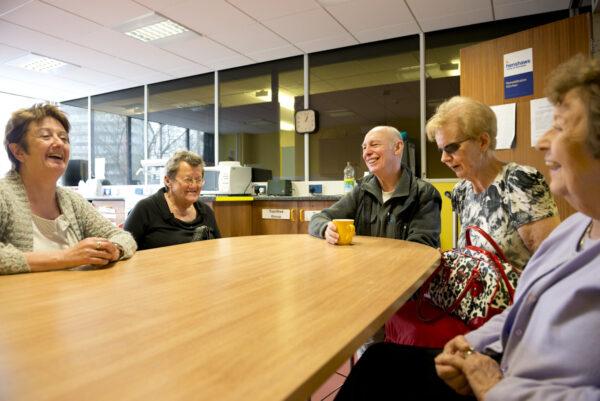 Group of Henshaws volunteers around a table