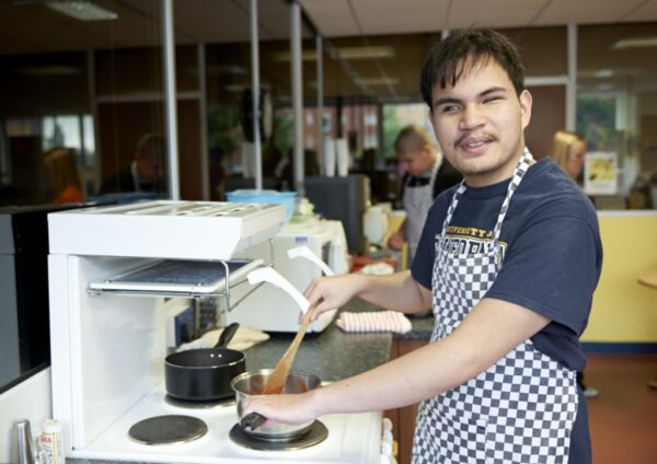 Visually impaired man stood cooking in a kitchen