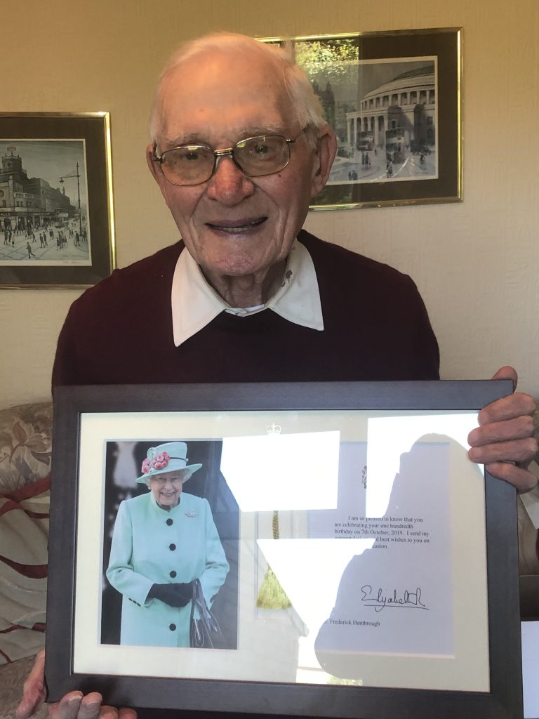 Image shows an elderly gentleman holding a framed certificate which has a photo of the Queen alongside a congratulatory message to Fred for turning 100 years old.