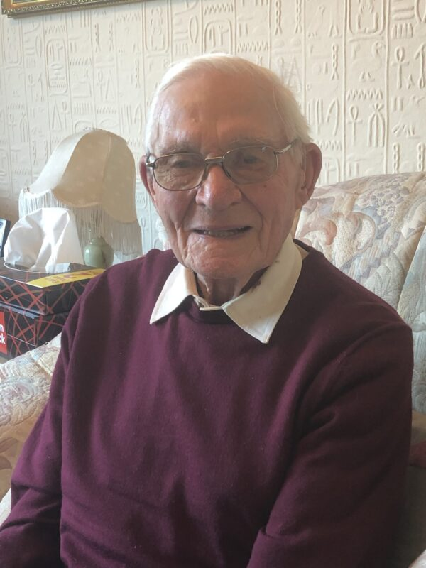 Image shows an elderly gentleman looking at the camera and smiling.