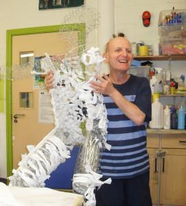 Photo of art maker holding up a sculpture